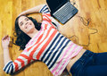 Beautiful teenage girl listening to the music while lying on floor Royalty Free Stock Photo