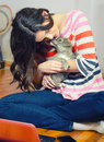 Beautiful teenage girl playing with small dog puppy having fun in her room notebook while holding Royalty Free Stock Images
