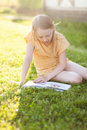Beautiful teenage girl reading book and sitting on green grass