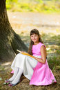Beautiful teenage girl reads the book under huge Royalty Free Stock Photo