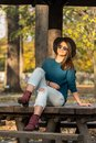 Beautiful teenage girl sitting on the park bench with black hat blue sweater and ripped jeans with blurred autumn leaves in the ba Royalty Free Stock Photo