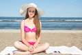 Beautiful teenager in pink bikini and white hat sitting on the b sandy beach Royalty Free Stock Photos