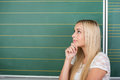 Beautiful thoughtful young student or teacher standing in front of a black green chalkboard with her hand to her chin staring Royalty Free Stock Images