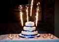 Beautiful three-layered wedding cake with fireworks Royalty Free Stock Photo