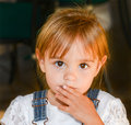 Beautiful toddler with big eyes looks at the camera a in a lace shirt and overalls Royalty Free Stock Photo