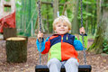 Beautiful toddler boy having fun on swing in autumn forest Royalty Free Stock Photo