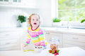 Beautiful toddler girl with curly hair having breakfast wearing a colorful shirt drinking juice in a white sunny kitchen a Stock Photo