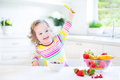 Beautiful toddler girl with curly hair having breakfast wearing a colorful shirt drinking juice in a white sunny kitchen a Royalty Free Stock Photo