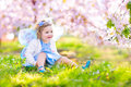 Beautiful toddler girl in fairy costume in fruit garden