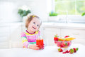 Beautiful toddler girl having breakfast drinking juice with curly hair wearing a colorful shirt in a white sunny kitchen with a Stock Photos
