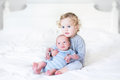 Beautiful toddler girl holding her newborn baby brother on a whi white bedroom Stock Photography