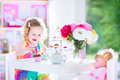 Beautiful toddler girl playing tea party with a doll adorable curly hair wearing colorful dress on her birthday toy dishes cup Stock Images