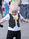 Beautiful toddler walking with his mother on a city holiday. Kid stylishly dressed butterfly and cap. Boy holding Royalty Free Stock Photo