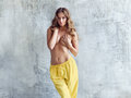 Beautiful topless girl wearing yellow pants posing in studio Royalty Free Stock Photo
