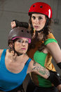 Beautiful and tough roller derby skaters two with helmets Royalty Free Stock Image