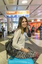 Beautiful tourist girl with backpack and carry on luggage in int Royalty Free Stock Photo