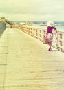 Beautiful traveler lady in red walking near the sea in retro style Royalty Free Stock Images