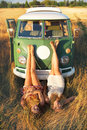 Beautiful traveling attractive women lying in the grass in front of an old caravan bus Stock Images