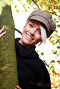 Beautiful trendy woman relaxing outdoors young blond with a lovely friendly smile and stylish cap holding onto the trunk of a tree Royalty Free Stock Images