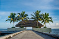Beautiful tropical landscape with wooden hut on bridge with palm trees near the ocean at Maldives Royalty Free Stock Photo