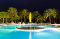 Beautiful tropical swimming pool with palm trees in evening scenery Royalty Free Stock Photos