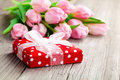 Beautiful tulips with red polka dot gift box happy mothers day romantic still life fresh flowers on wooden background Royalty Free Stock Images