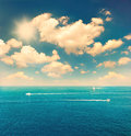 Beautiful turquoise sea water and perfect blue sky with white clouds retro style image Royalty Free Stock Images