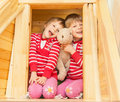 Beautiful twin sisters two cheerful girls twins playing on the second floor of a wooden house Stock Photo