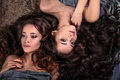 Beautiful twins young women with natural make-up and hair style lying with their curly hair surround them