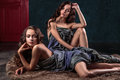 Beautiful twins young women with natural make-up and hair style posing naked covered with grey cloth Royalty Free Stock Photo