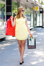 Beautiful urban girl walking on the street after shopping down sunny summer day Royalty Free Stock Photos