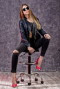 Beautiful urban trendy girl in black leather jacket and jeans posing on a high chair Royalty Free Stock Photo