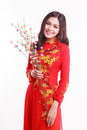 Beautiful Vietnamese woman with red ao dai holding cherry blossom