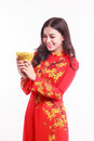 Beautiful Vietnamese woman with red ao dai holding lucky new year ornament - stack of gold Royalty Free Stock Photo