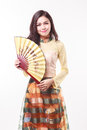 Beautiful Vietnamese young woman with modern style ao dai holding a paper fan Royalty Free Stock Photo