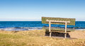 The beautiful view of bench on grass looking out toward the ocea ocean beach with sky in new zealand Royalty Free Stock Images