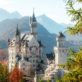 Beautiful view of world-famous Neuschwanstein Castle with Alpine mountains on Background, under sunlit. Wonderful sunny landscape Royalty Free Stock Photo