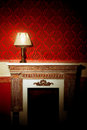 Beautiful vintage interior with lamp on fireplace old in red room Royalty Free Stock Image