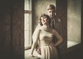 Beautiful vintage style couple standing near window Royalty Free Stock Image