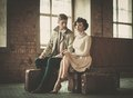 Beautiful vintage style couple young with suitcases on a train station Royalty Free Stock Photo