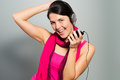 Beautiful vivacious woman listening to music on headphones connected a handheld electronic storage device as she stands Stock Images
