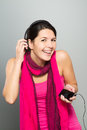Beautiful vivacious woman listening to music on headphones connected a handheld electronic storage device as she stands Stock Image