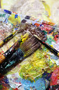 Beautiful vivid art palette and mix of paintbrushes in fresh paint Stock Image