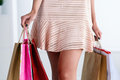 Beautiful walking legs of a woman in dress holding colored paper Royalty Free Stock Photo