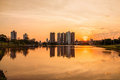A beautiful warm sunset at the lake with buildings and the city background. Scene reflected on water. Royalty Free Stock Photo