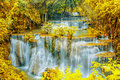 Beautiful  waterfall in autumn forest with ray light. Royalty Free Stock Photo