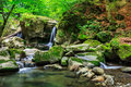 Beautiful waterfall comes out of a huge rock in the forest incredibly and clean little with several cascades over large stones Royalty Free Stock Photography