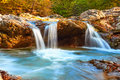 Beautiful waterfall in forest at sunset. Autumn landscape, fallen leaves
