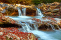 Beautiful waterfall in forest at sunset. Autumn landscape, fallen leaves Royalty Free Stock Photo