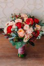 Beautiful wedding bouquet of red flowers, pink flowers and greenery is on the wooden floor. Royalty Free Stock Photo